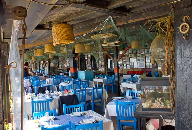 Interior of Pepe Fishing Club, Byblos, complete with blue painted chairs and dangling fishing nets.