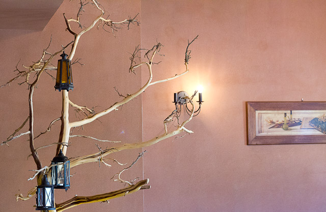 Detail of interior of Sto Kioupi: nude tree with lanterns.