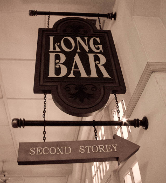 Sign points the way to the Long Bar at Raffles Hotel, Singapore.