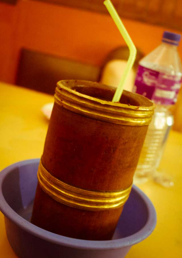 A bamboo cup with gilded nodes, containing tongba hot beer.