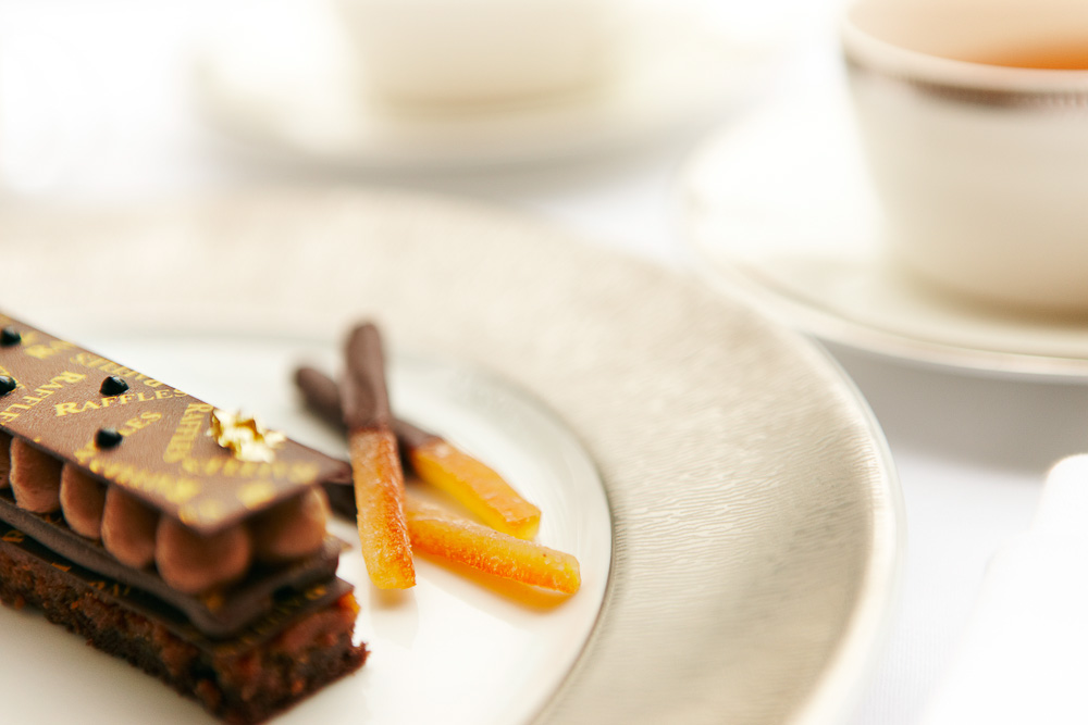 Cakes and chocolate-coated ginger at Raffles high tea.