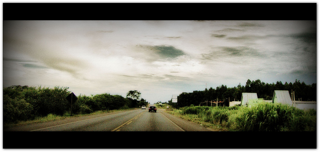 Car on deserted highway below a cloudy sky.