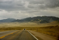Open road curves across the plains to dramatic highlands.