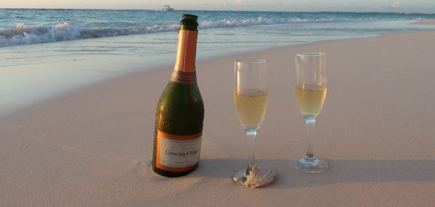 Champagne and glasses on the sand.