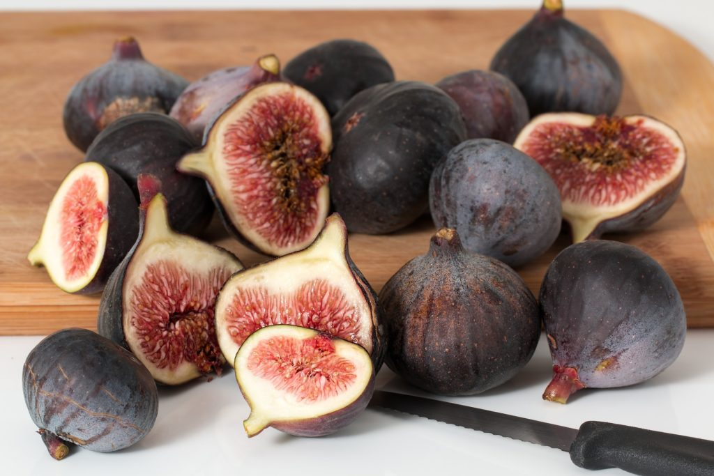 Ripe figs on a chopping board with a knife.
